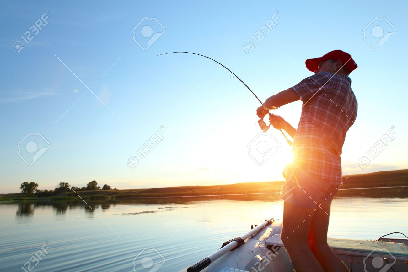 Young man fishing on a lake from the boat at sunset - 23509926