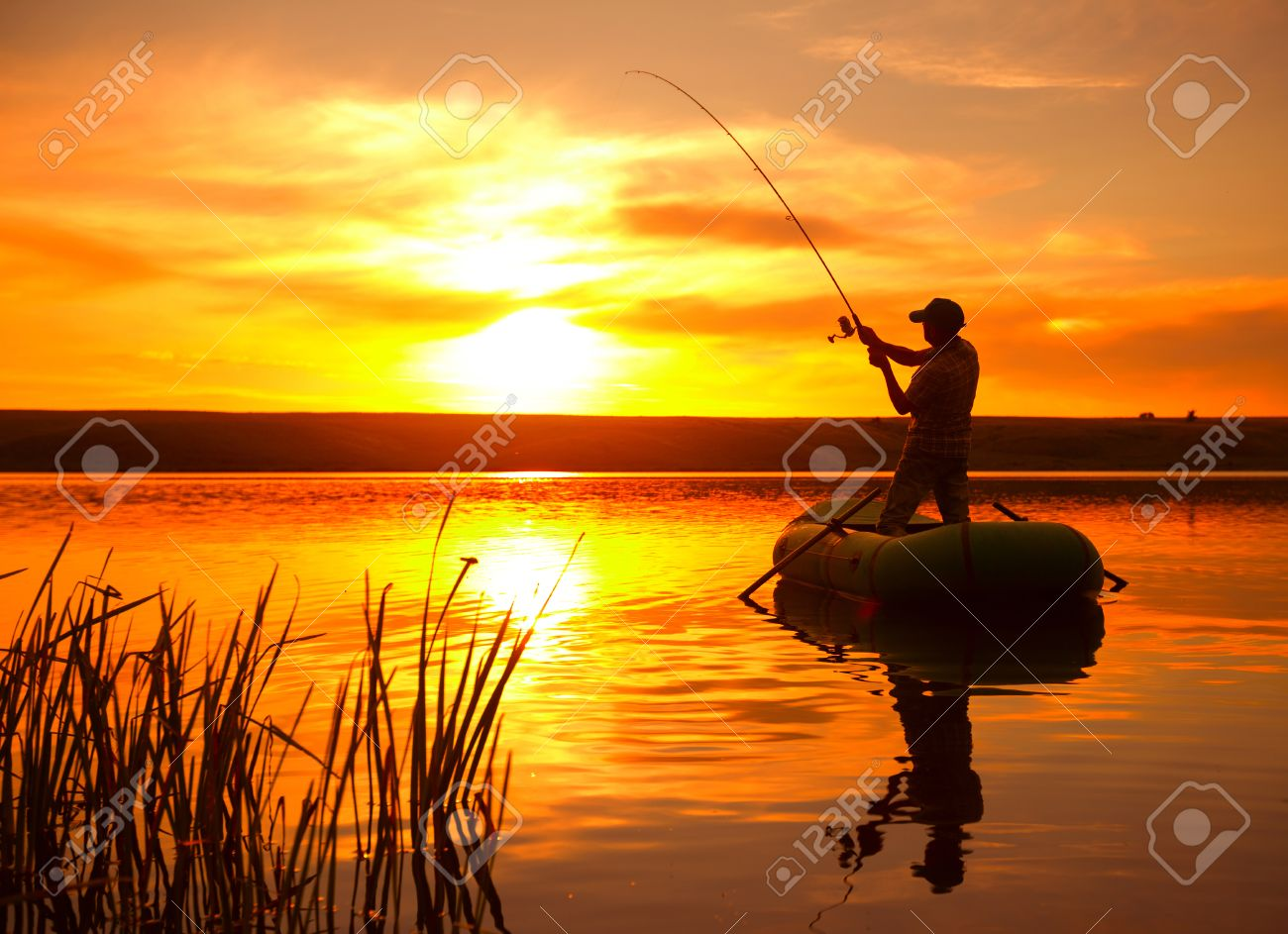 Mature man fishing from the boat on the pond at sunset - 31259752