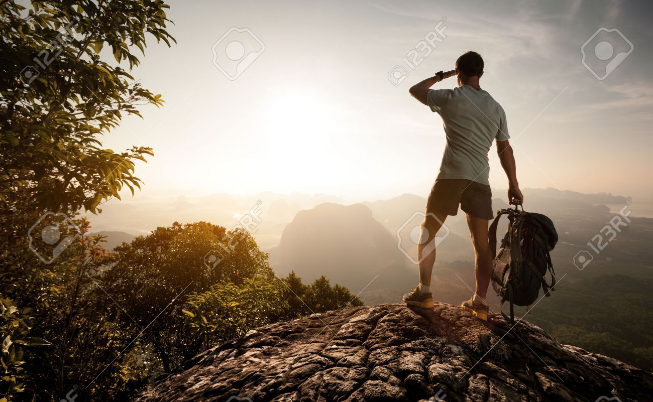 Hiker on top of the mountain enjoying sunrise over the tropical valley - 35423685