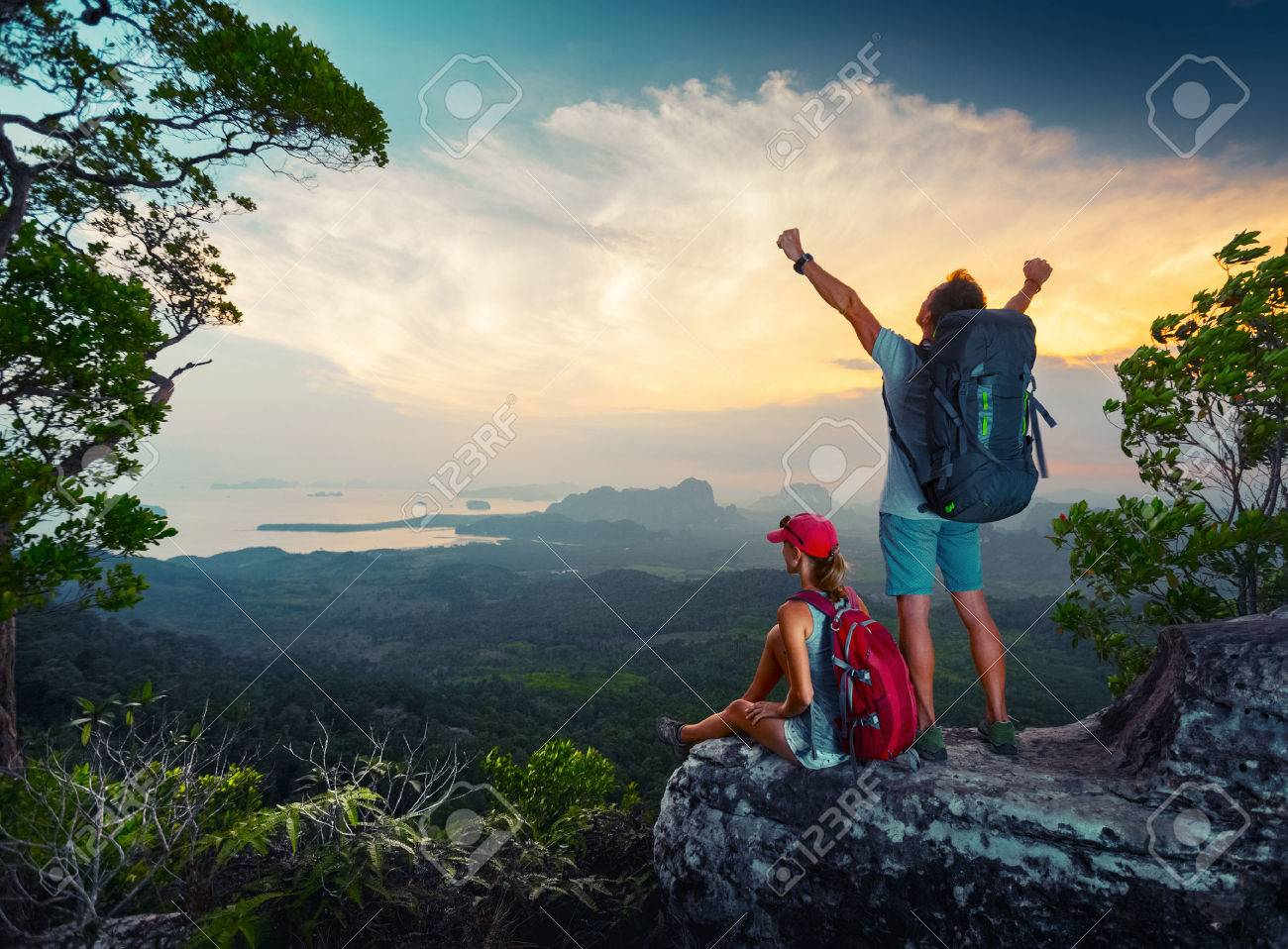 Two hikers relaxing on top of the mountain and enjoying sunset valley view - 48201130