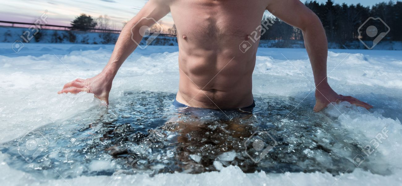 Young man bathing in the ice hole. Focus on the ice in a water only - 50602570