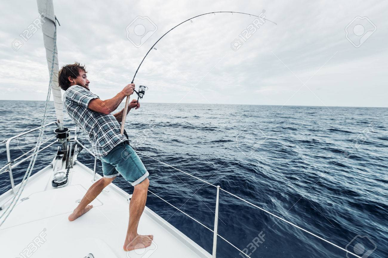 Young man fishing hard in open sea from sail boat - 54786118