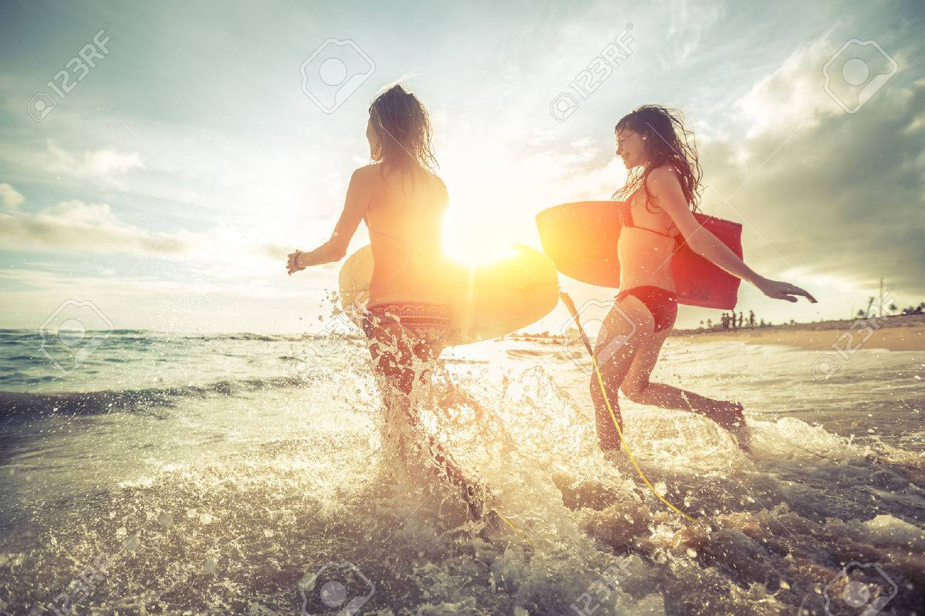 Two young women running into the sea with surf boards Stock Photo - 55065844