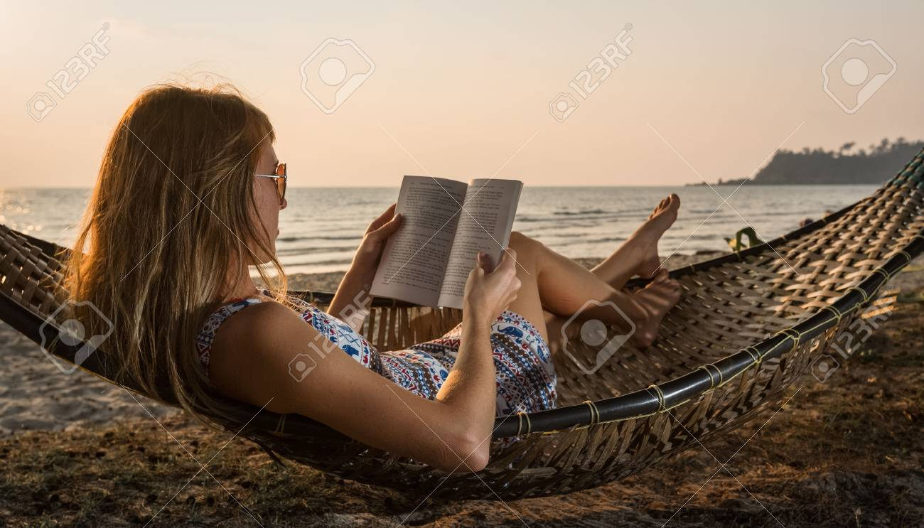 Young lady reading a book in hammock on a beach at sunset - 56103219