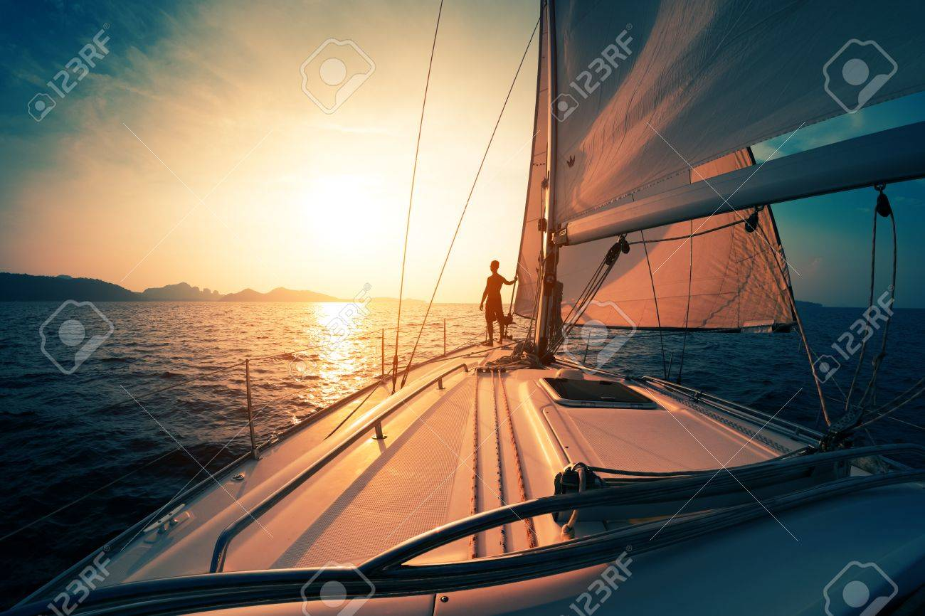 Young man on the sailing boat at sunset - 61996447