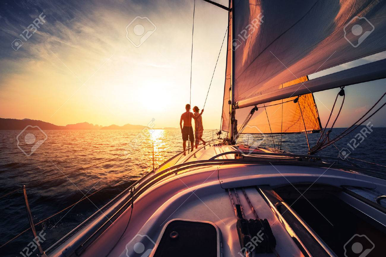 Couple on the sailing boat at sunset - 61996449