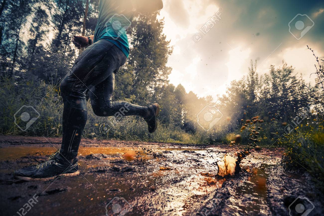 Trail running athlete crossing the dirty puddle in the forest - 62477827
