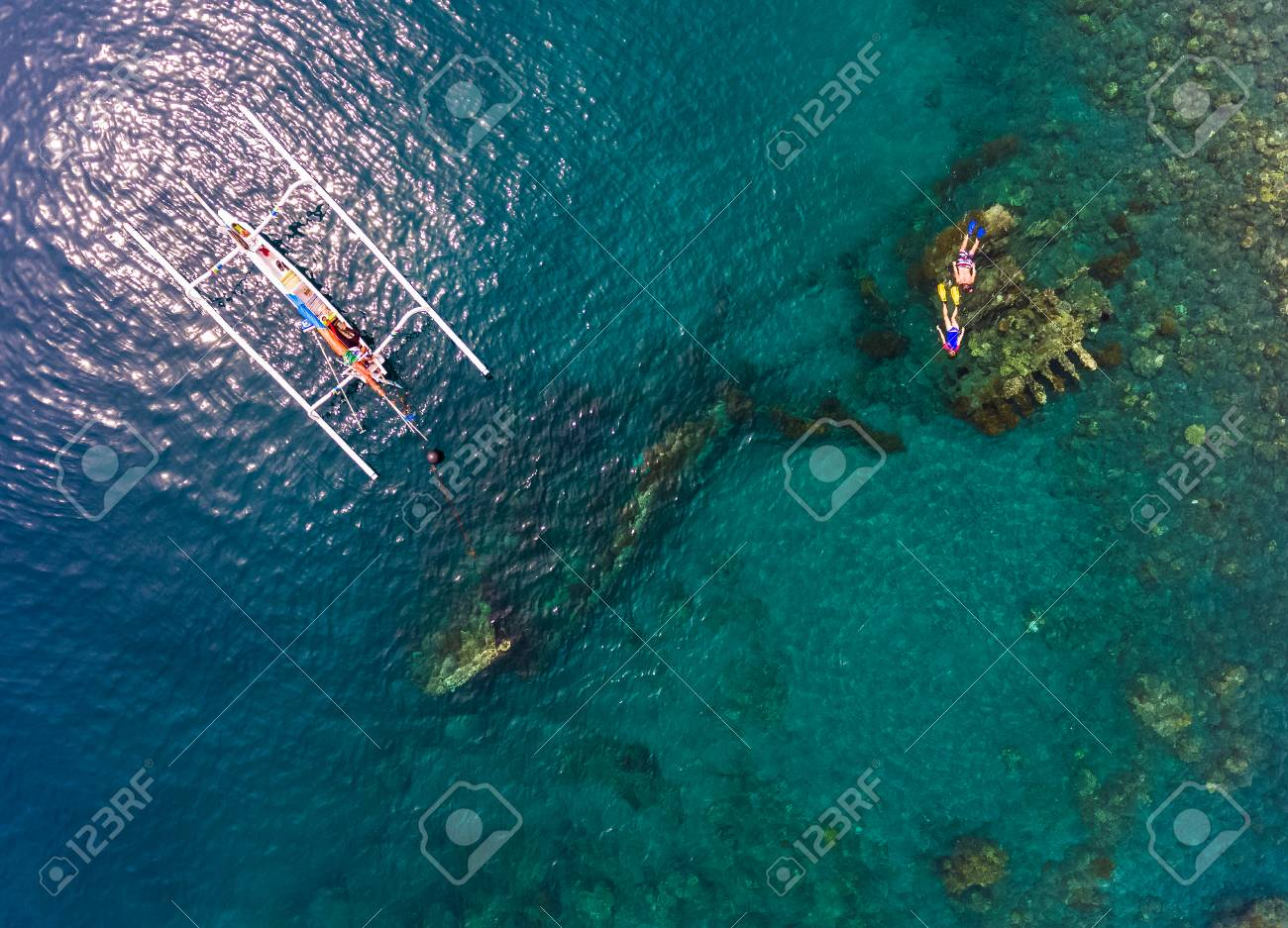 Aerial Shot Of The Japanese Ship Wreck With Boat And People Snorkeling Over It Bali