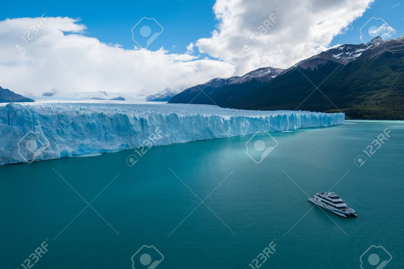 Front part of the Perito Moreno Glacier located in the Southern Patagonian Ice Field and touristic, day trip boat on the turquoise Lago Argentino. Argentina - 105015343
