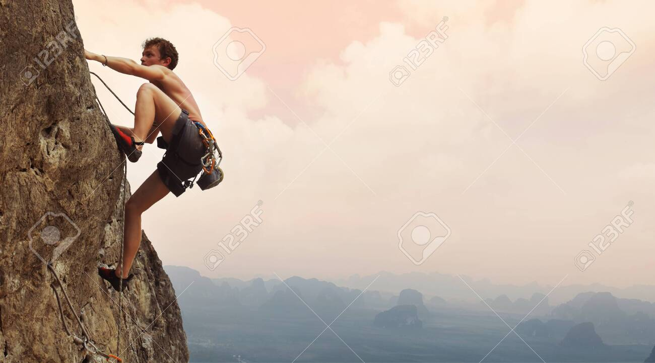 Young man climbing on a limestone wall with wide valley on the background - 123633685
