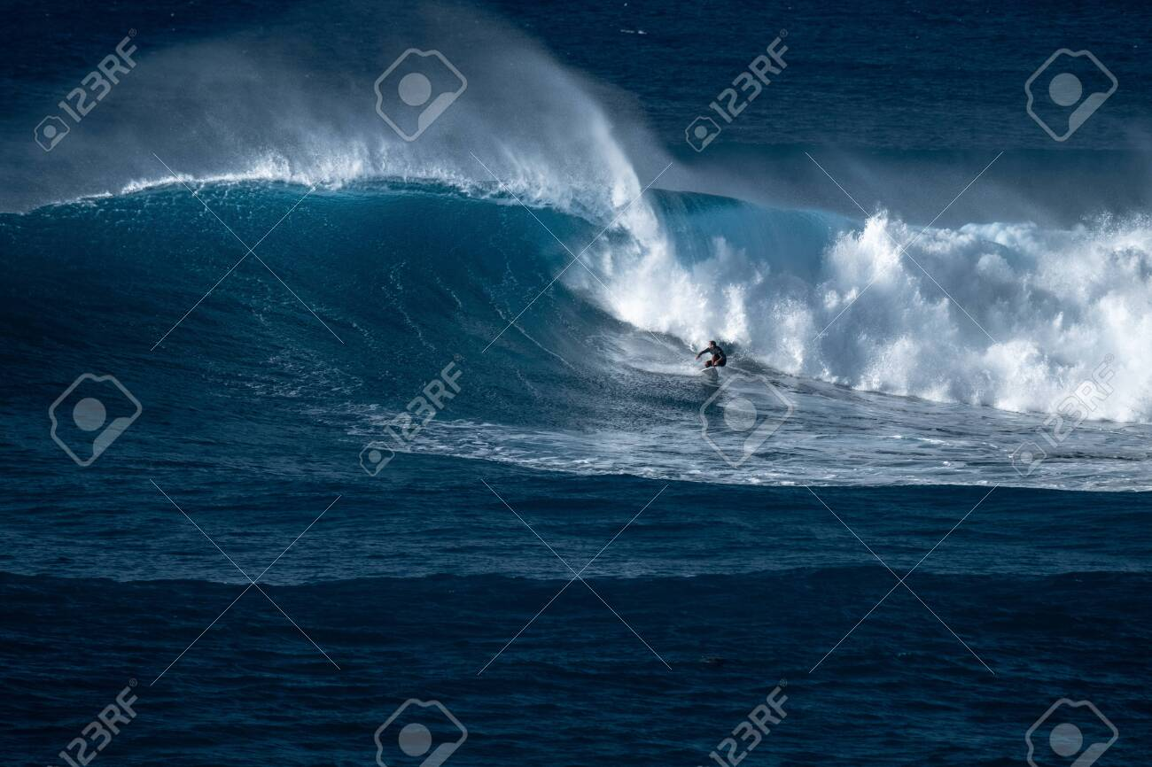 Surfer rides giant wave at the famous Waimea Bay surf spot located on the North Shore of Oahu in Hawaii - 125488299