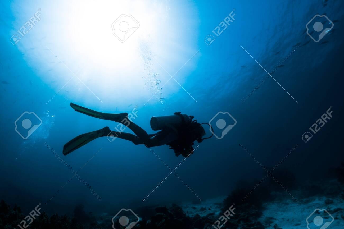 Silhouette of the scuba diver swimming alone in the depth - 125235960
