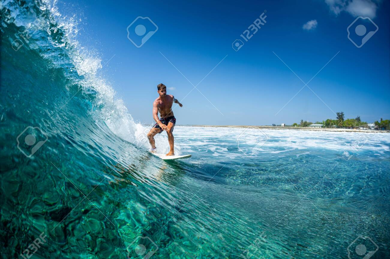 Surfer rides ocean wave in tropics - 137277249
