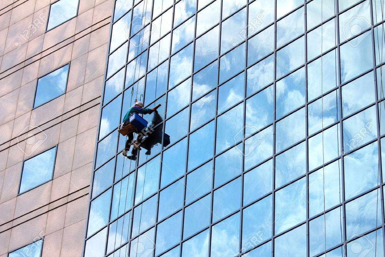 window cleaner hanging on rope at work on skyscraper Stock Photo - 9937231