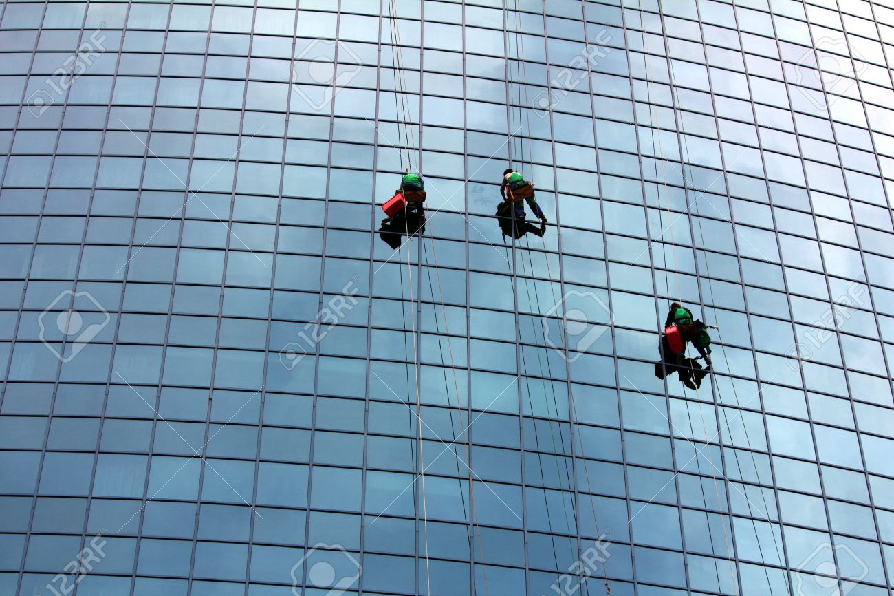window cleaners hanging on rope at work on skyscraper - 9937234