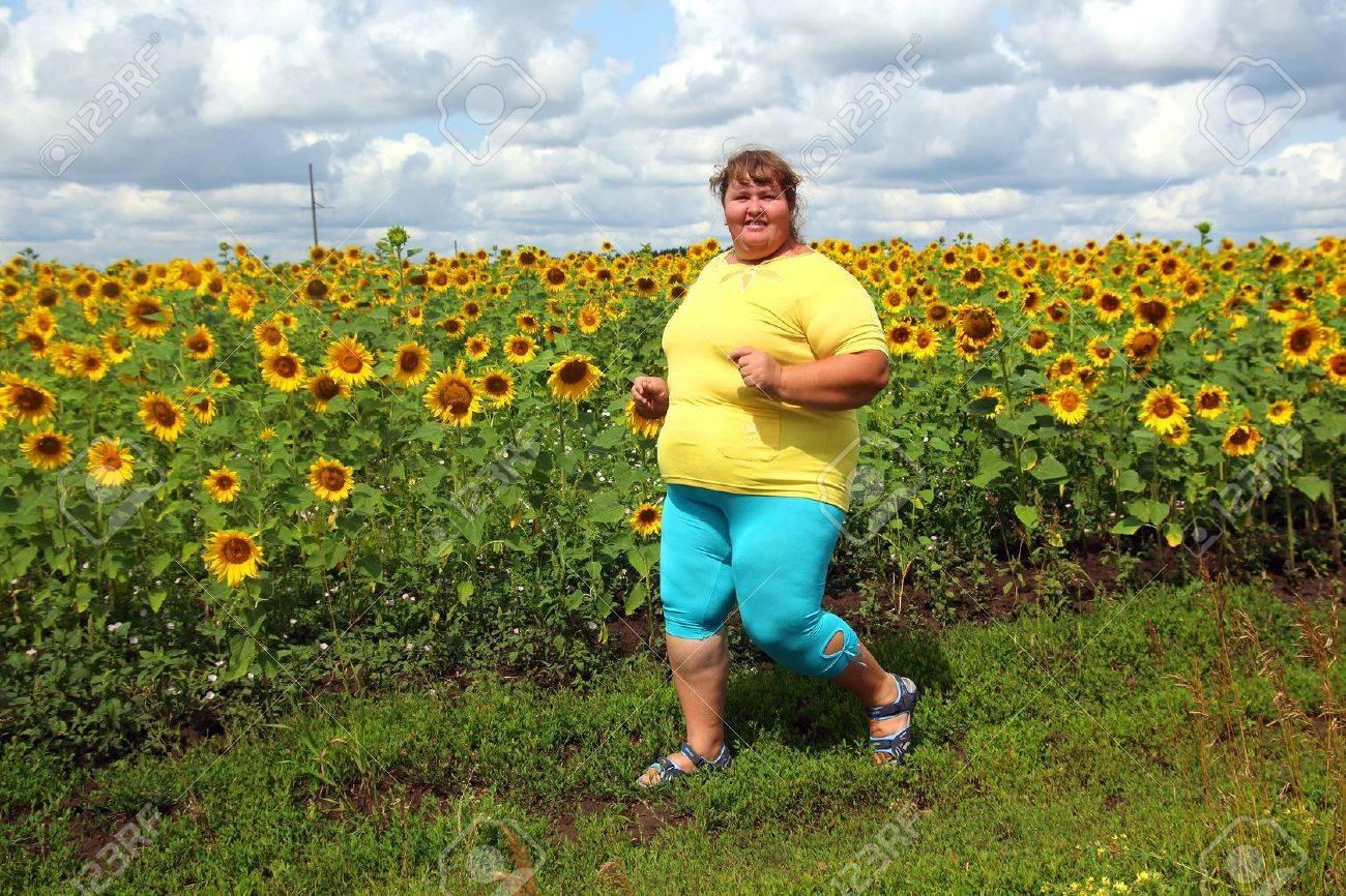 fitness - overweight woman running along field of sunflowers - 21172782