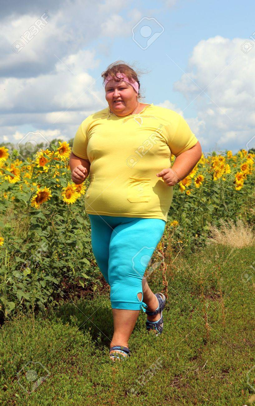 fitness - overweight woman running along field of sunflowers - 21172783