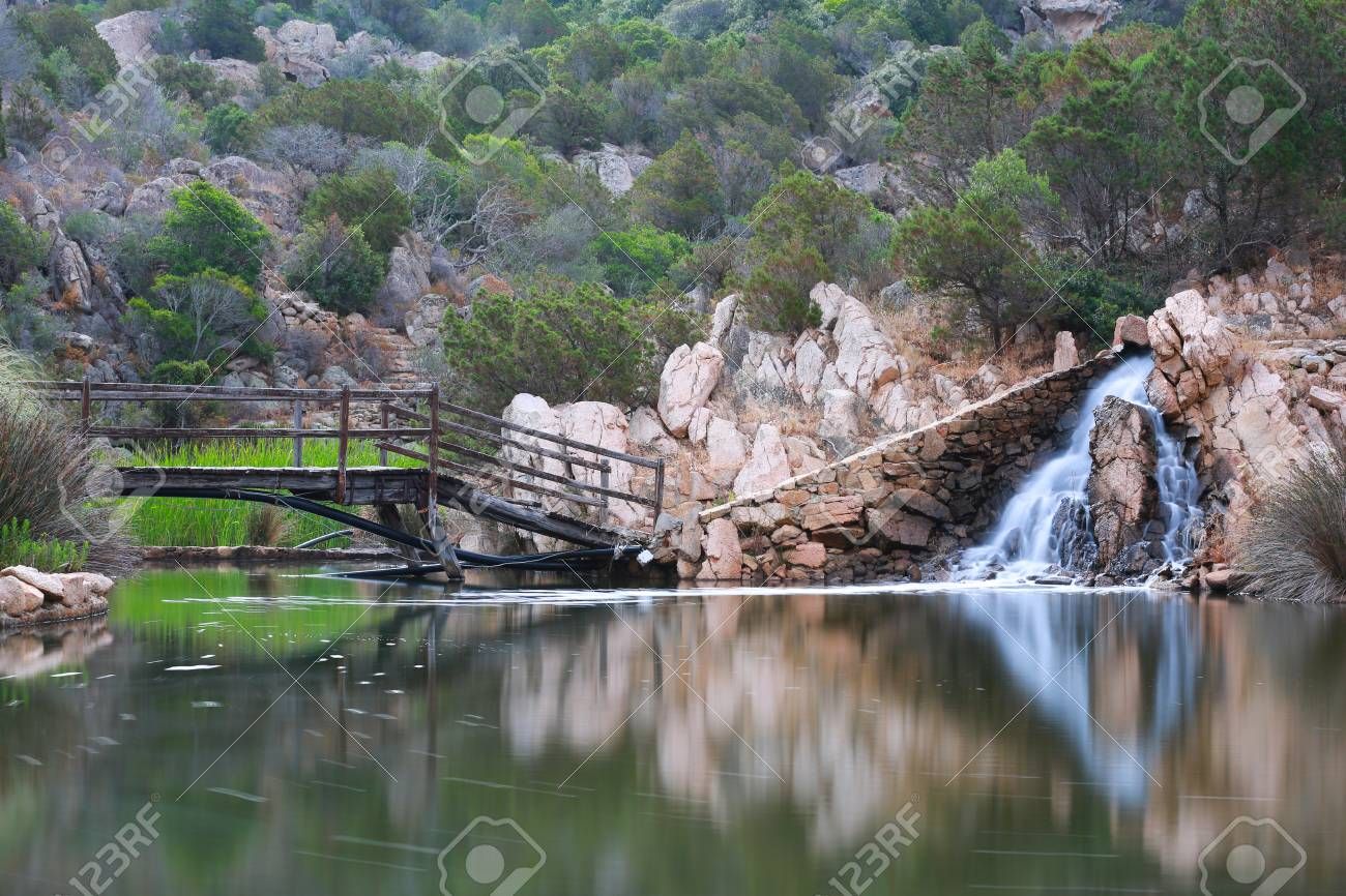 An Old Wooden Bridge Crossing To A Waterfall At A Pond In Sardinia