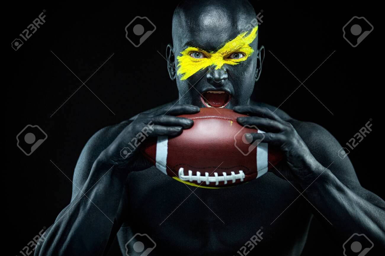 American football fan with ball on black background. Fitness and sport motivation. Strong fit and athletic guy in body paint like a super hero. - 145573560