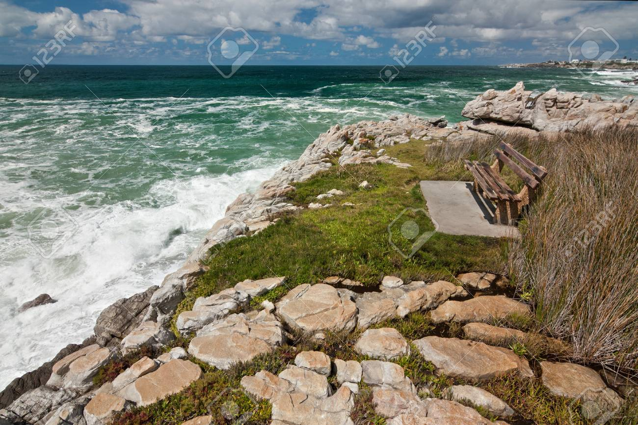 view of the foamy ocean shoreline with a bench grass and rocks Stock Photo - 16685393