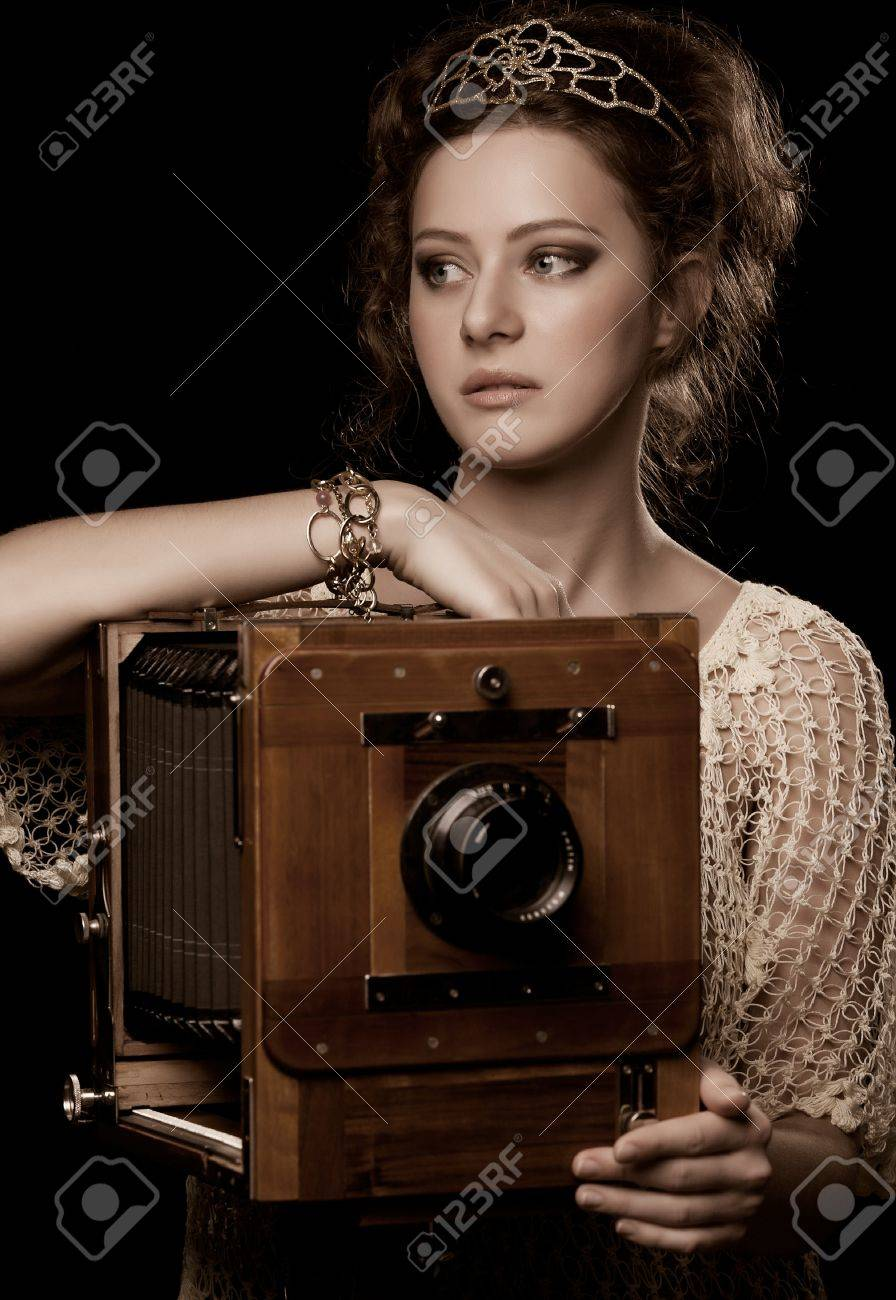 young woman standing near the old-fashioned camera Stock Photo - 8778142