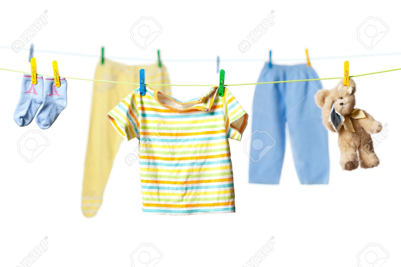 Baby clothes and a tearful teddy bear drying on a rope isolated on white background Stock Photo - 11784401