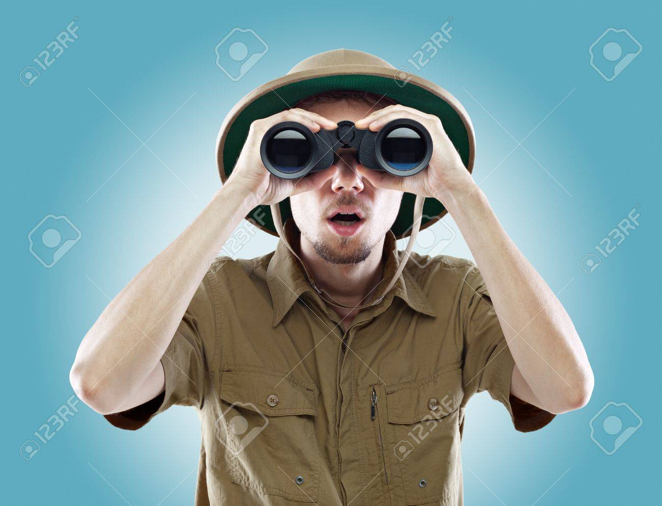 Young man wearing a pith helmet looking through a pair of binoculars with a surprised expression, on blue background Stock Photo - 17394767