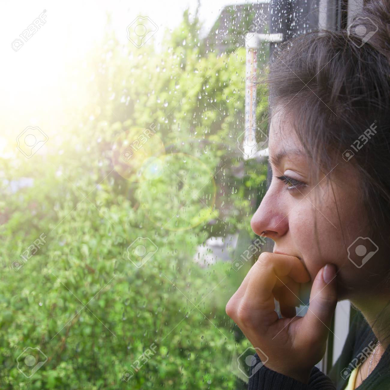 Sad girl looks out the window its raining. Woman with nice looking hear - 106640786