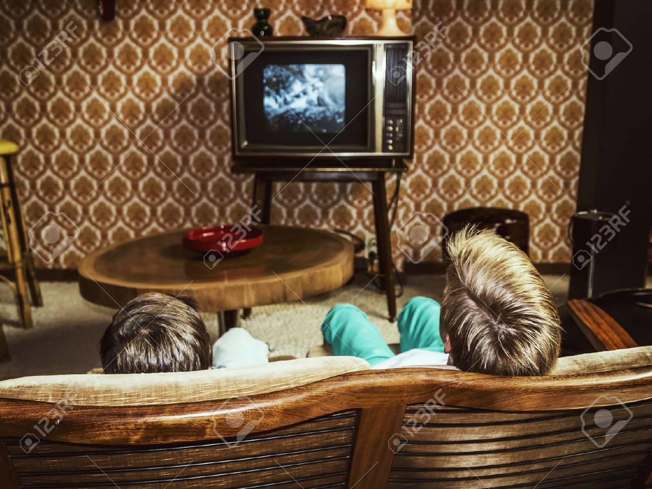 two boys watching television at home in 50's style, shot from behind - 53551237
