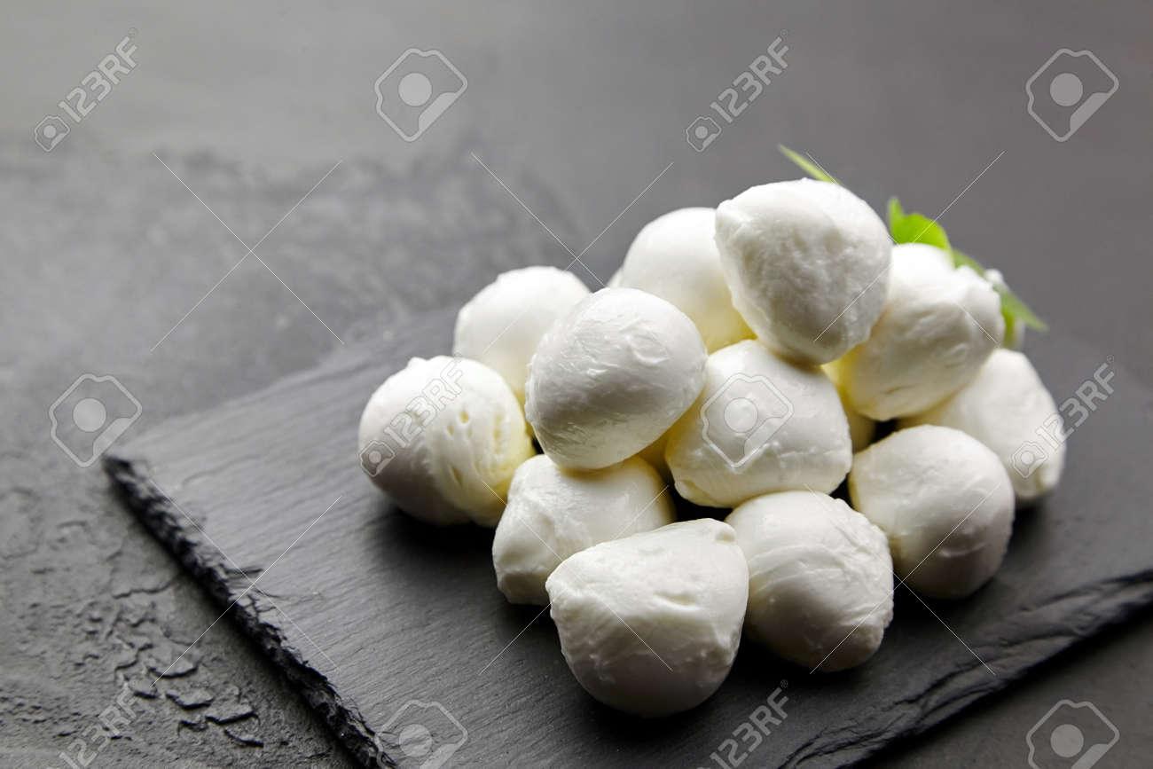 Small mozzarella cheese balls on black slate board over dark concrete background, italian food concept - 171676195