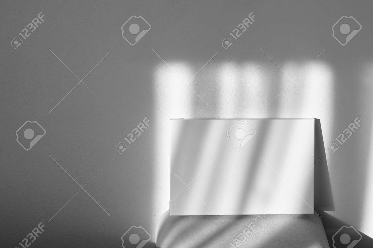 White canvas mockup on shelf on wall with shadows. Blank picture. Stretched cotton canvas - 171629541