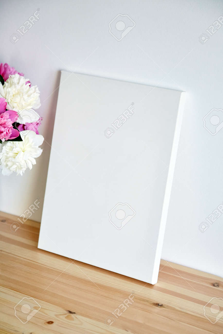 Canvas mockup with pink flowers on wooden table on white wall background. Blank artistic canvas - 171629656