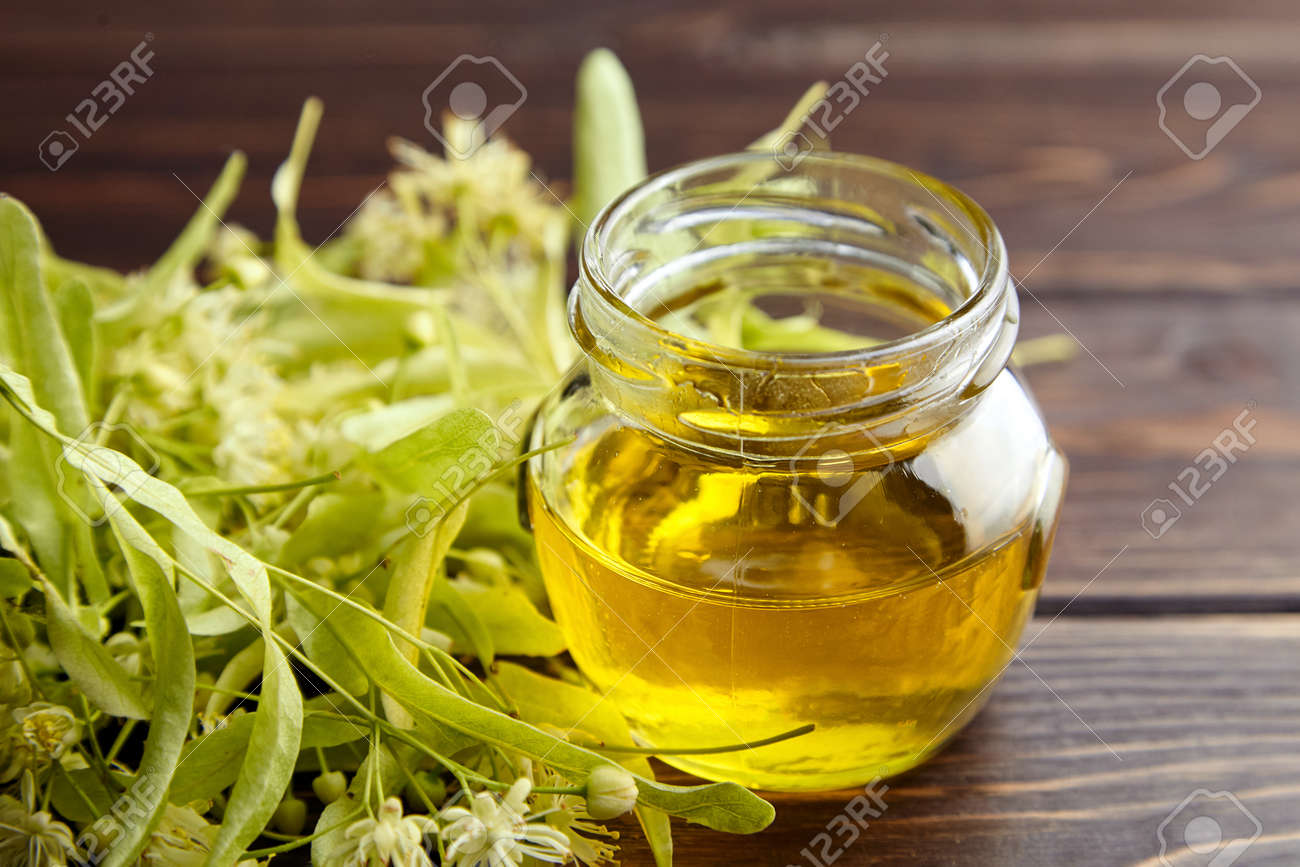 Linden honey in glass jar and linden flowers on wooden table. Sweet flower honey - 171629543