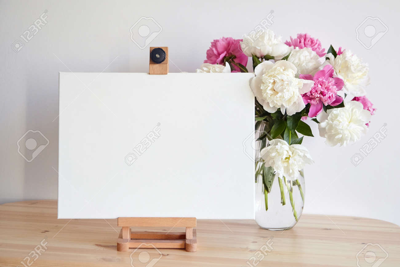 Canvas mockup on easel and pink flowers on wooden table on white wall background. Blank artistic canvas - 171629555