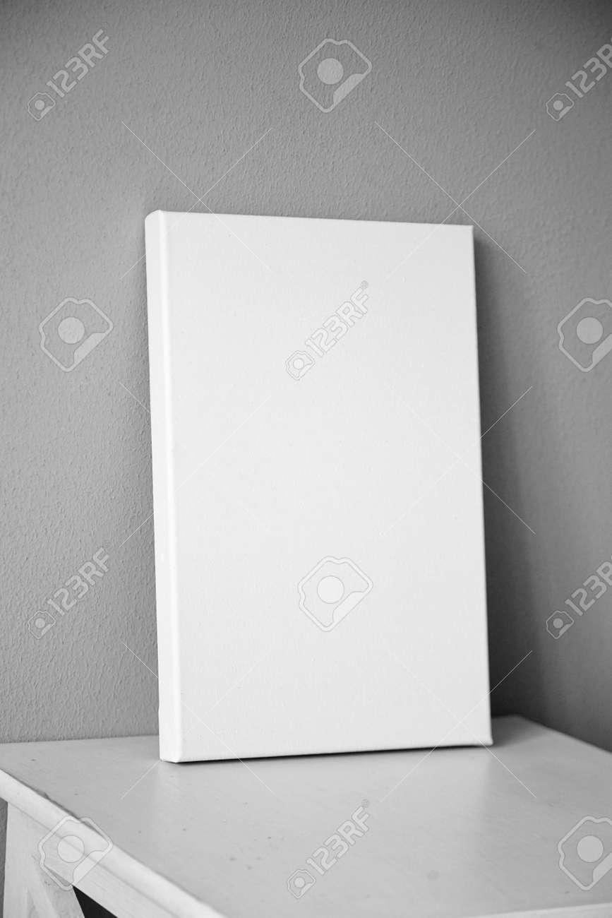 White canvas mockup, blank picture on white wooden table in interior with gray wall - 171629606