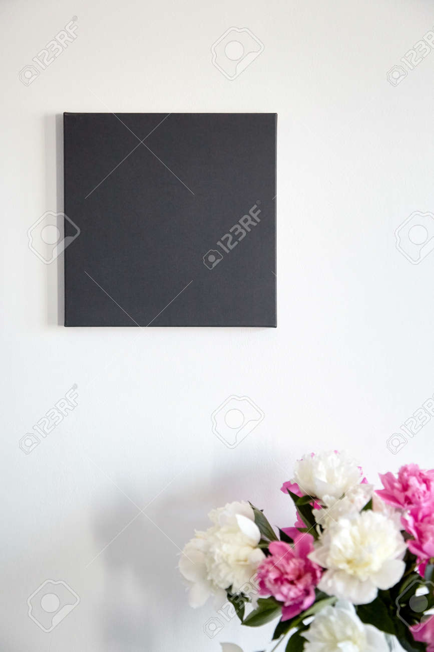 Black canvas mockup hanging on white wall and pink flowers. Blank artistic canvas - 171629832