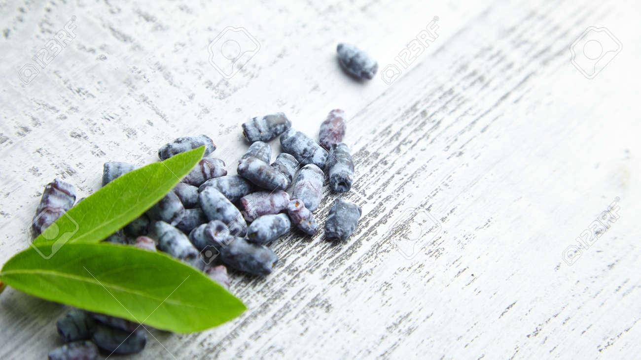 Honeyberry (Lonicera caerulea) on gray wooden background. Heap of sweetberry honeysuckle (Haskap berry) with fresh green leaves - 171676219