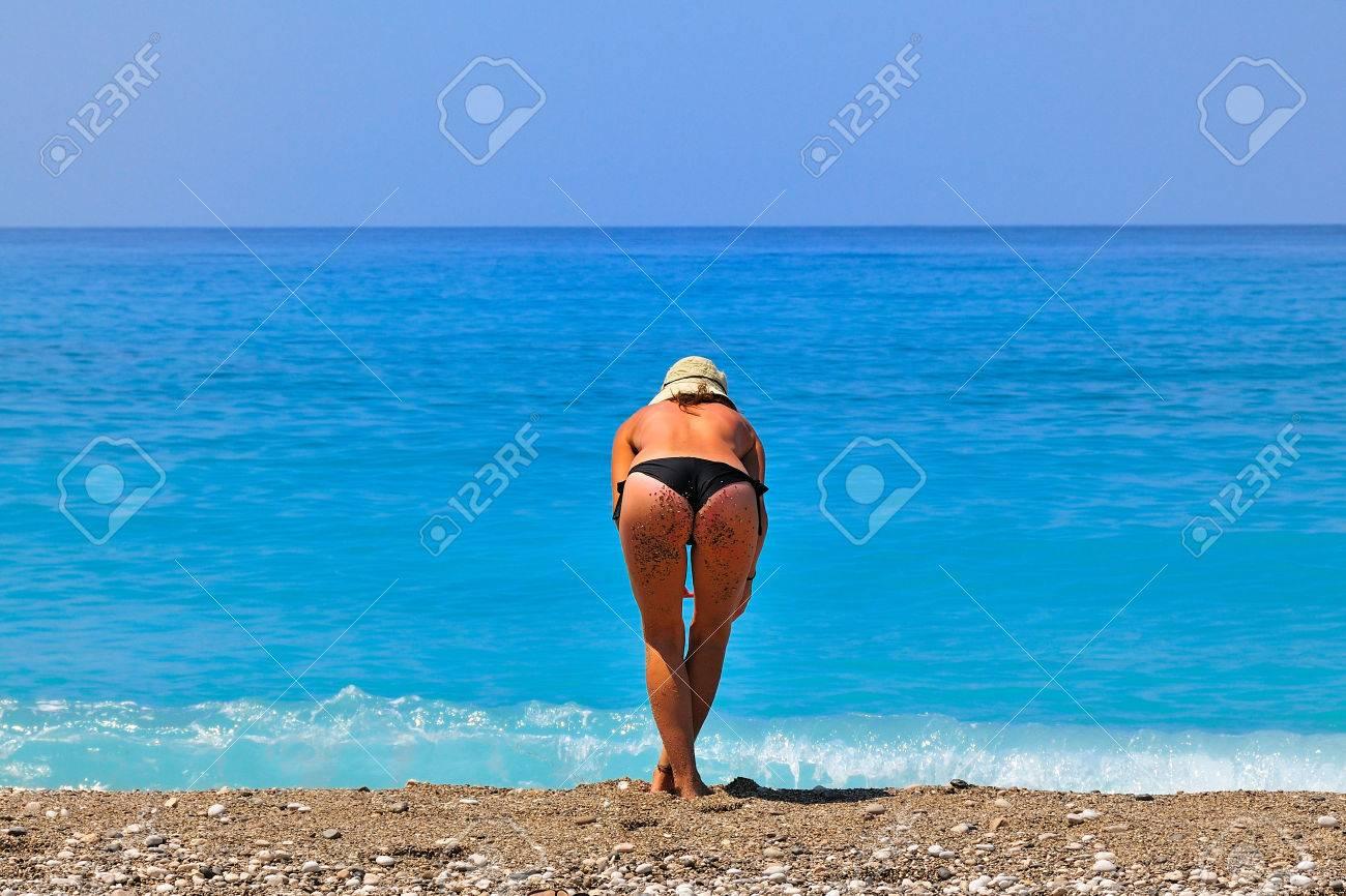 25ea8aa88d0d Detrás de la mujer caucásica joven quemada por el sol en un traje de baño  en topless con un sombrero, apoyándose en una playa.