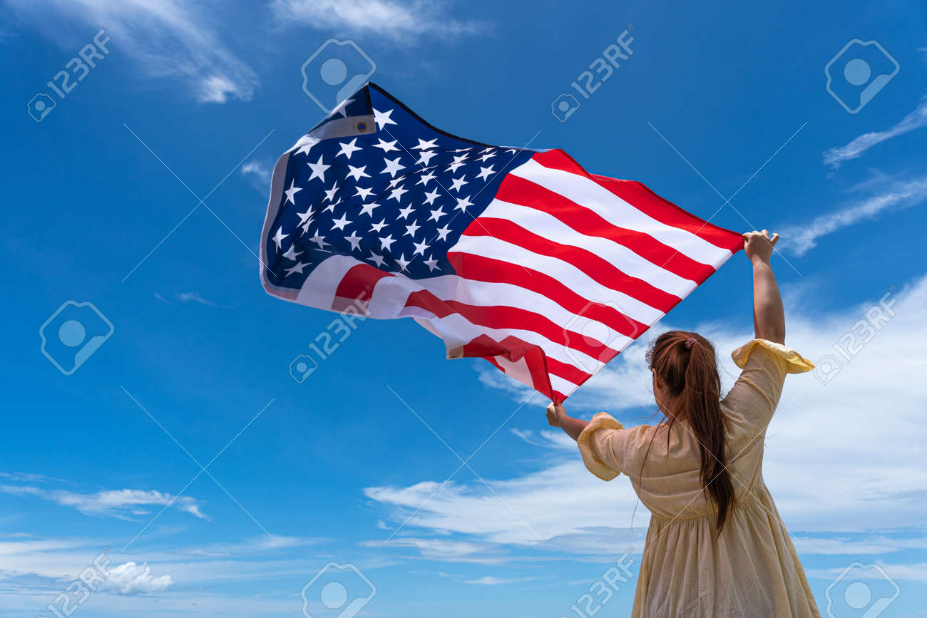 woman standing and holding USA flag under blue sky. - 154904085