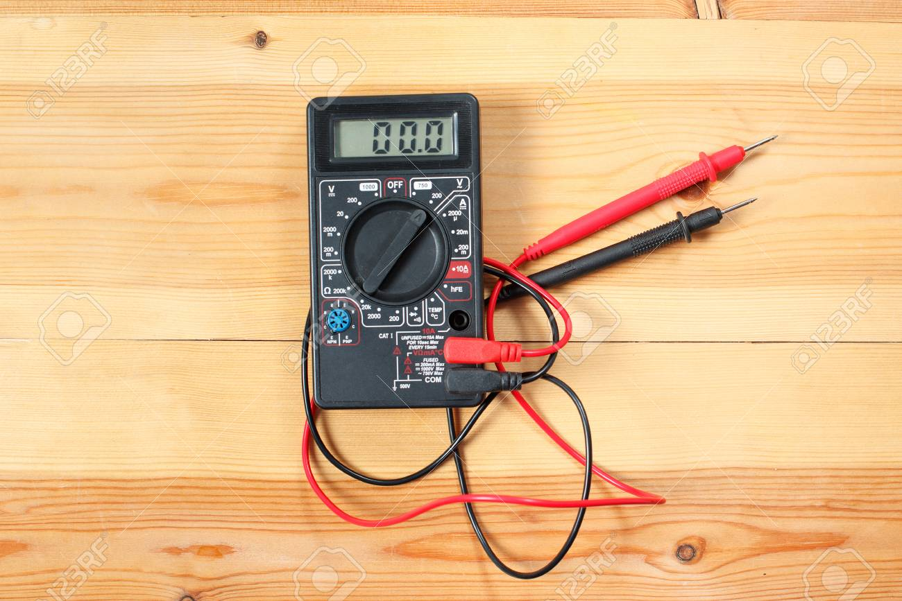 digital multimeter and wiring on wooden table. special tools.. on torque tools, framing tools, foundation tools, networking tools, insulation tools, programming tools, operation tools, three tools, pneumatic tools, power tools, precision tools, cutting tools, hand tools,