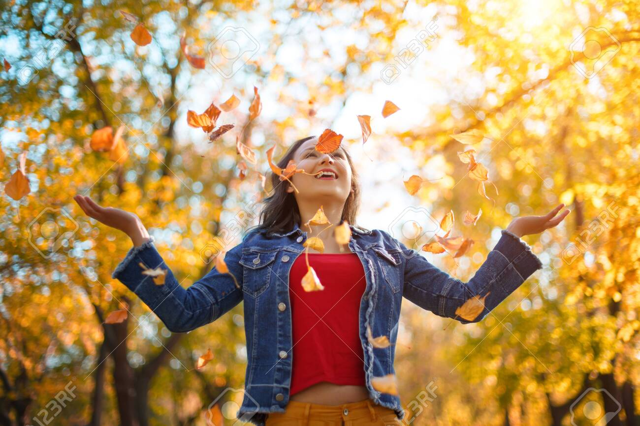 Portrait of a happy woman playing with autumn leaves in forest. autumn concept - 130503566