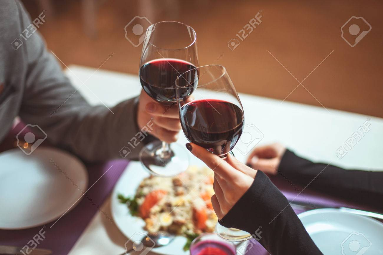 Beautiful young couple with glasses of red wine in luxury restaurant - 53982007