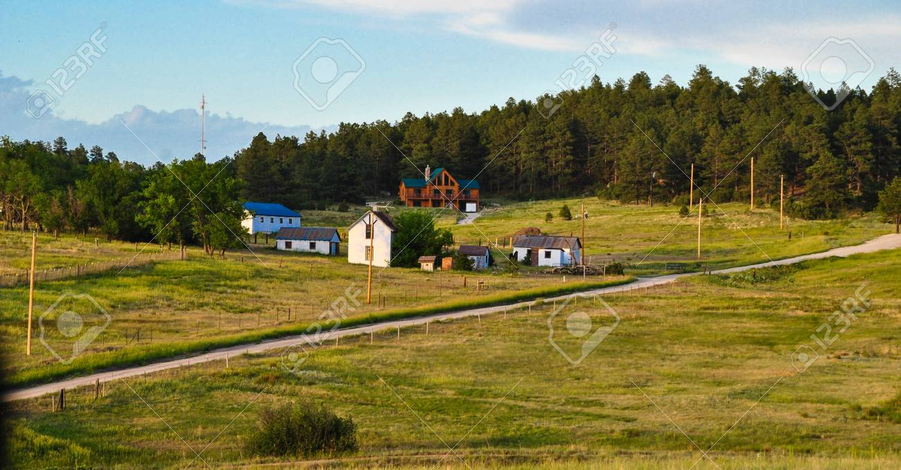 Country Farm With Hills In The Background And Grass Fields Under A Blue Sky Stock Photo