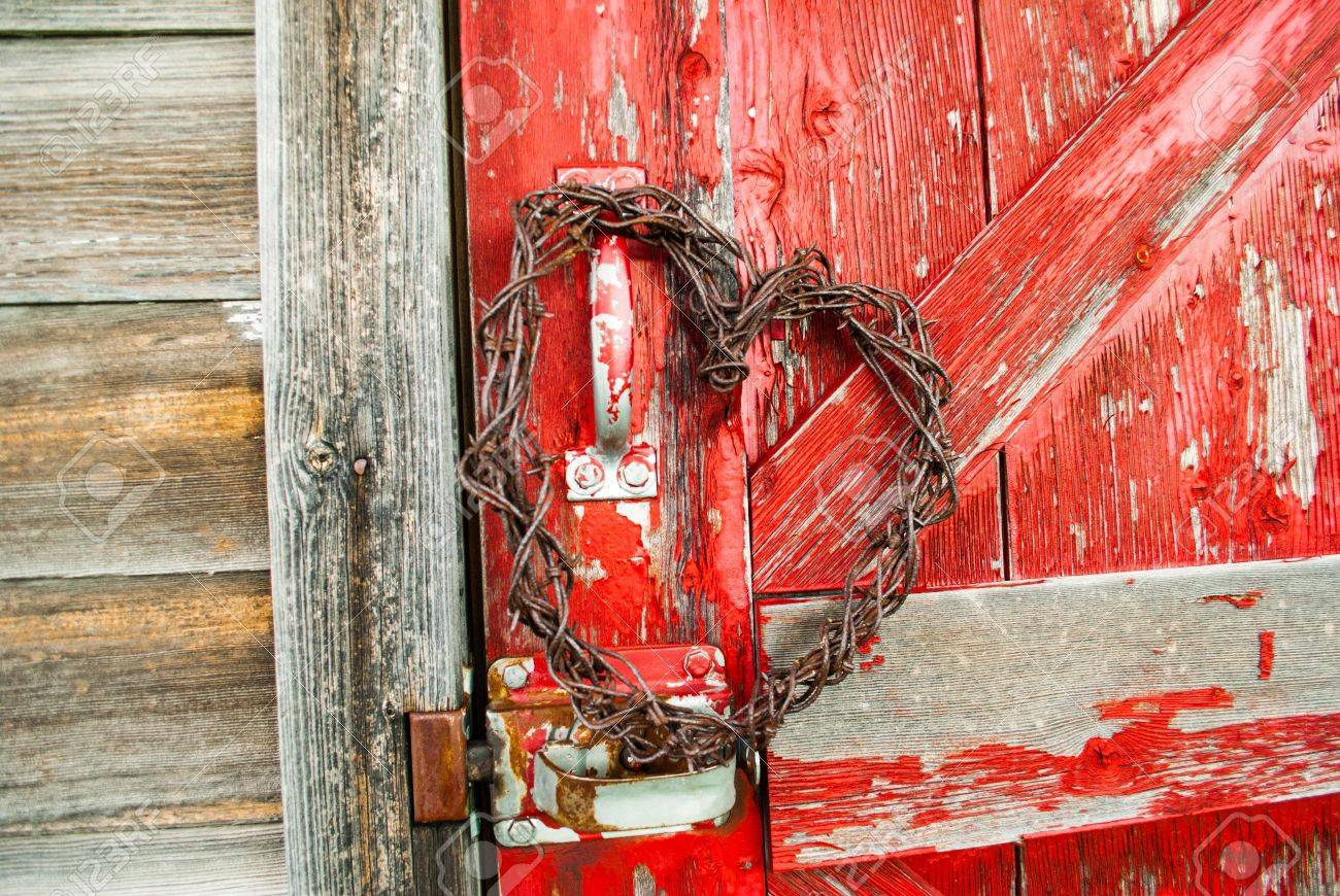 Red Barn Wood barbed wire heart hanging on old red barnwood door in sunlight