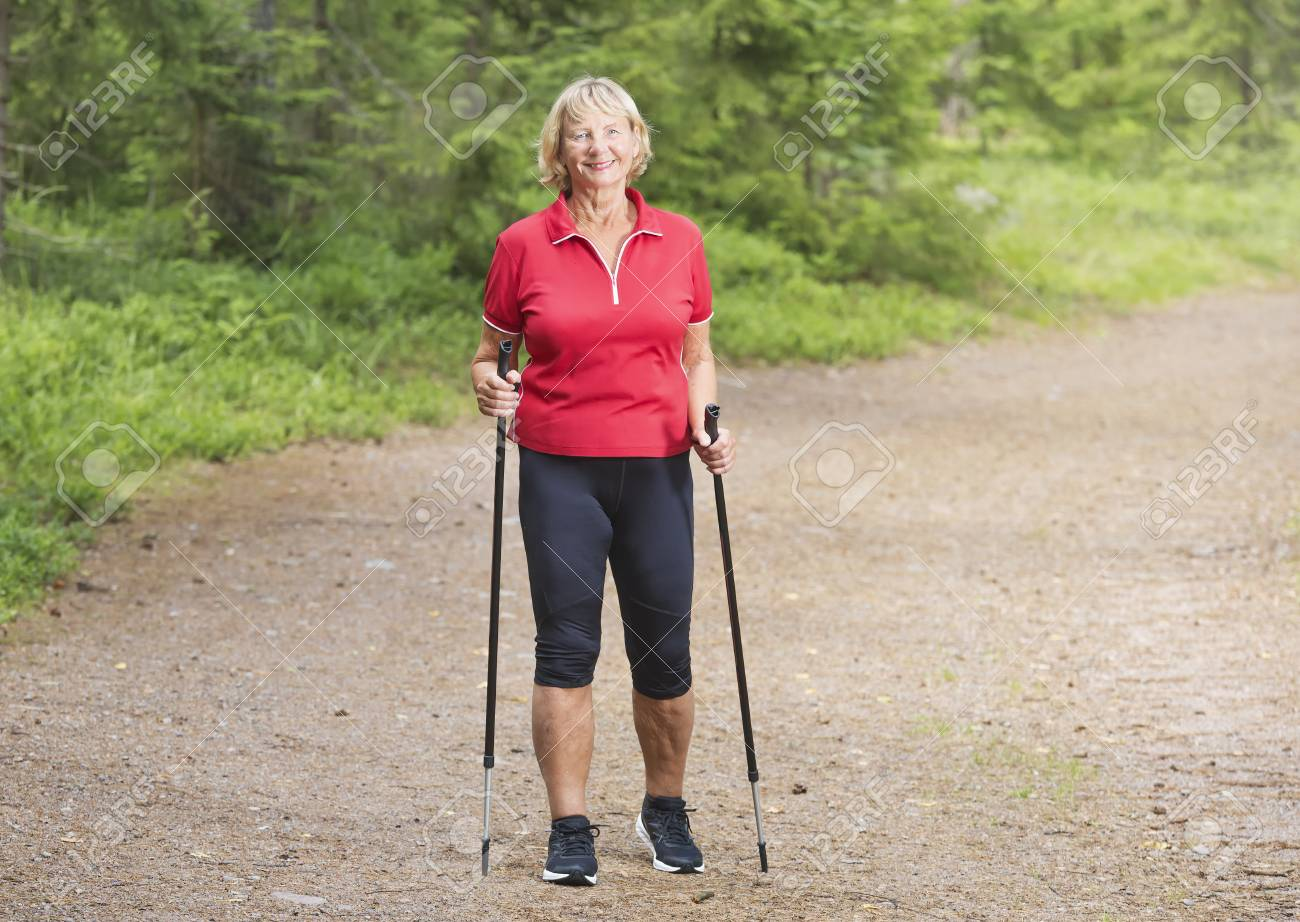 Front View Of A Happy Active Senior Woman Nordic Walking In The