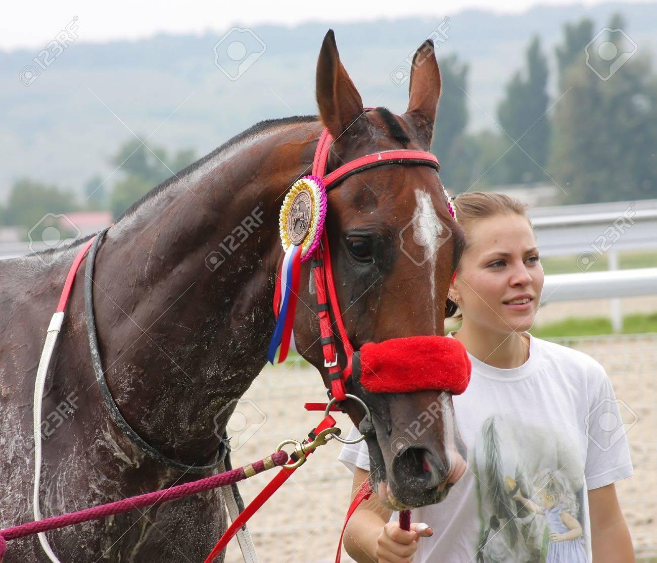 PYATIGORSK, RUSSIA - SEPTEMBER 4: An unidentified groom and akhal-teke horse, bay stallion Odjar after race for the prize of Drujbi narodov on September 4,2011 in Pyatigorsk, Caucasus, Russia.  Stock Photo - 10499719
