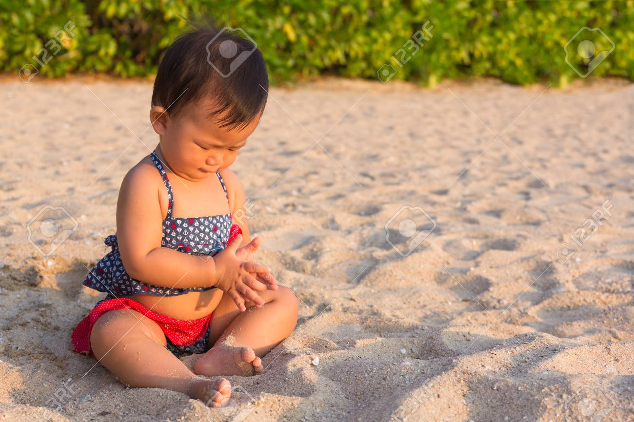 asian cute girl baby playing sand on the beach, sunset time