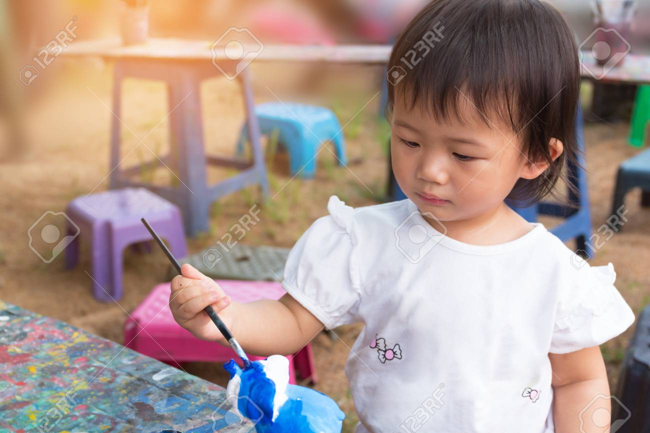 asian cute girl baby is painting colorful in the park. stock photo