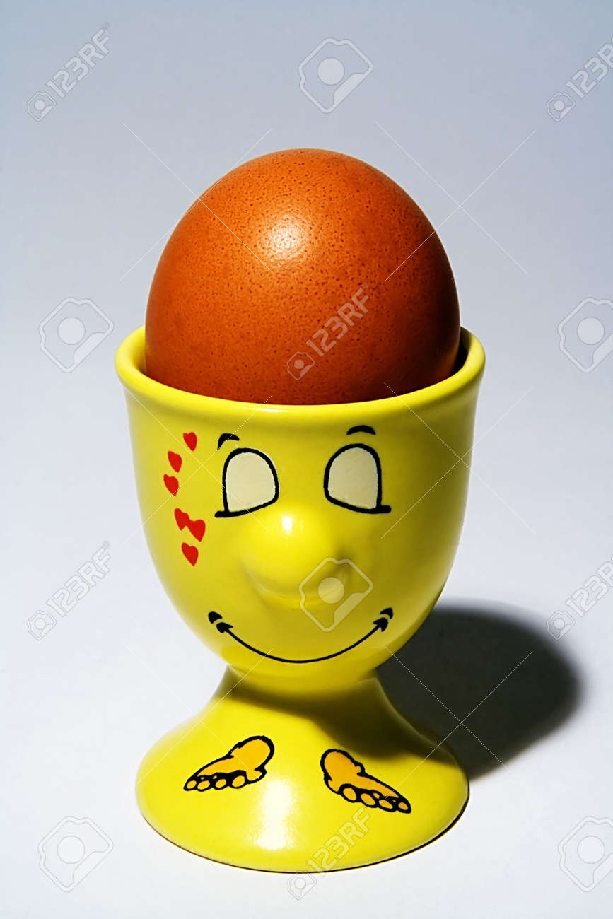 Egg in egg-cup with a smiling muzzle Stock Photo - 412498