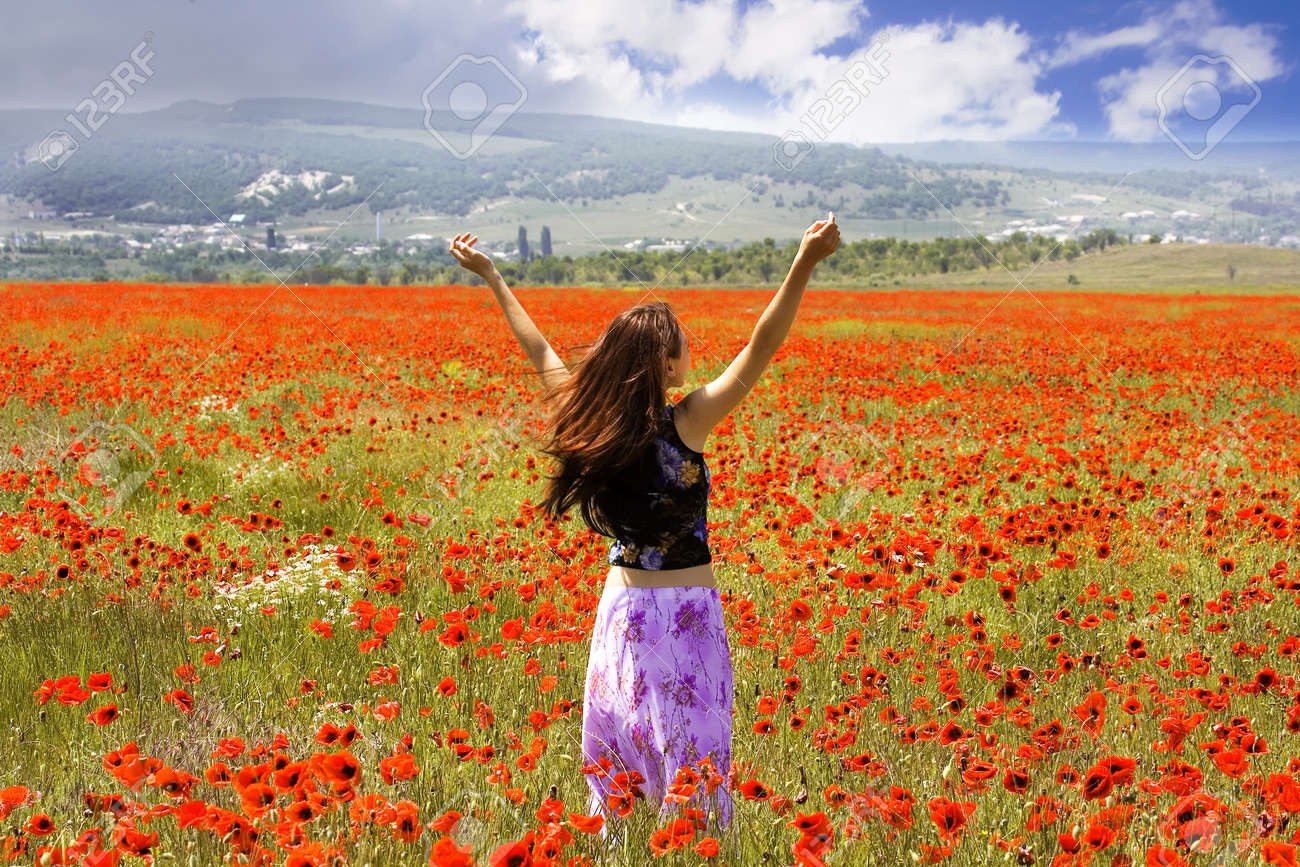 The girl on a meadow with blossoming poppies Stock Photo - 1080213
